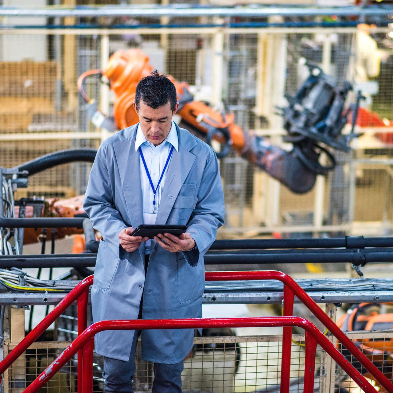 person holding tablet on floor of automated manufacturing warehouse