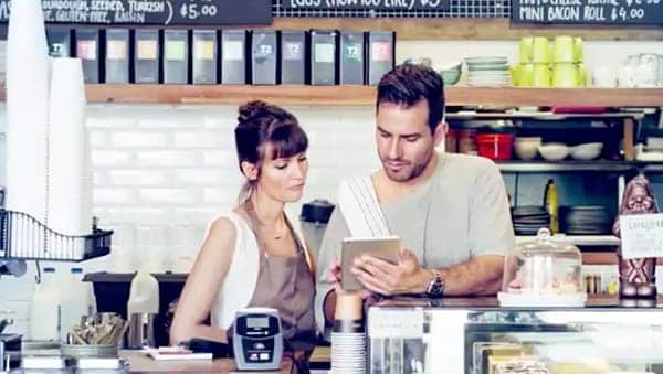Man and woman working behind the counter in a restaurant reviewing computer tablet.