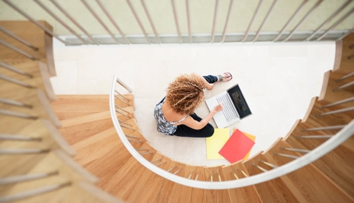 overhead down spiral stairs to a woman working on laptop and files