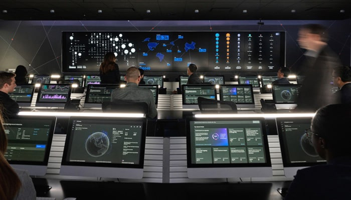 reverse angle of people in operations center looking at data screens