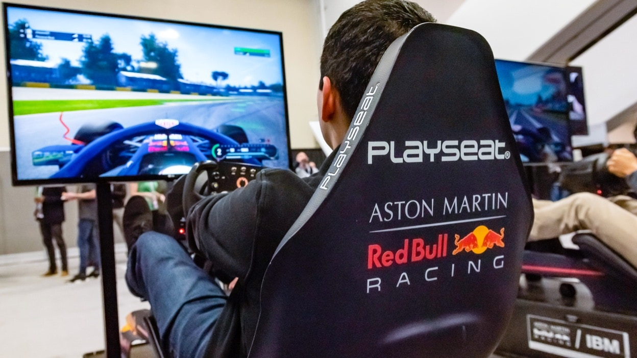 Driver from Aston Martin Red Bull Racing sitting in a racing simulation chair running a practice race