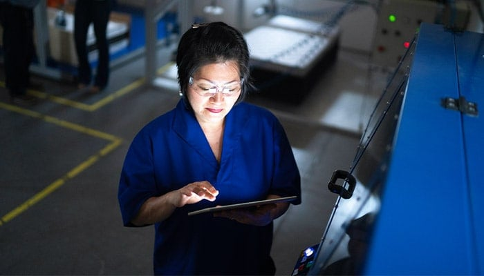 woman performing equipment diagnostics on a factory floor