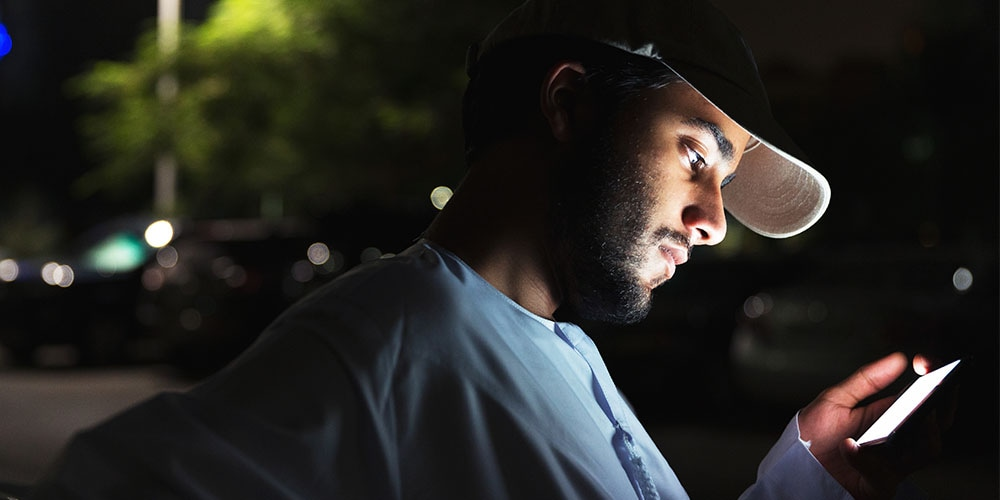 Man wearing hat looking at smartphone at night