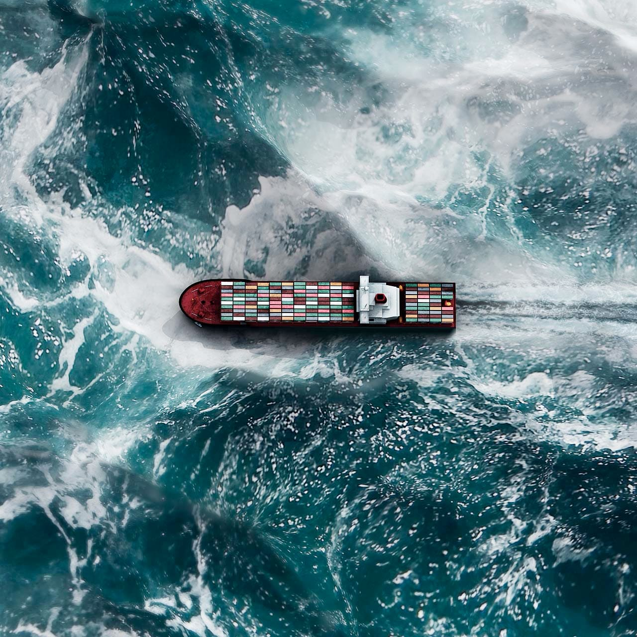 aerial shot of a barge afloat on a sea of crashing waves
