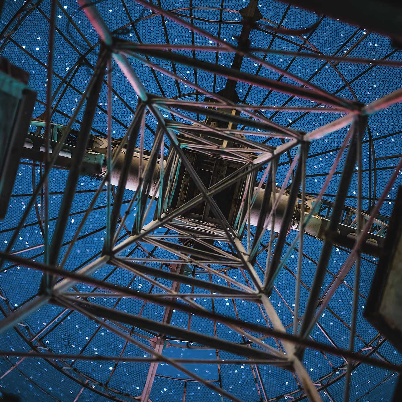 looking at a starry sky from below a radio telescope antenna
