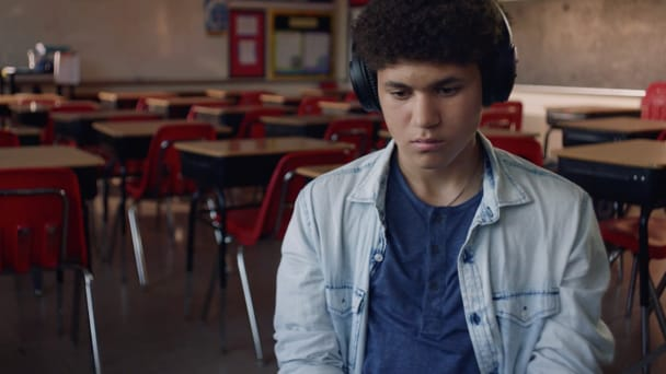 Student listening on headphones at school