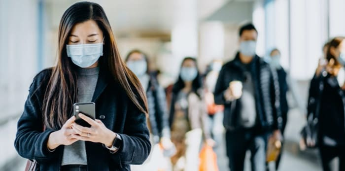 Girl wearing a mask while using her cellphone