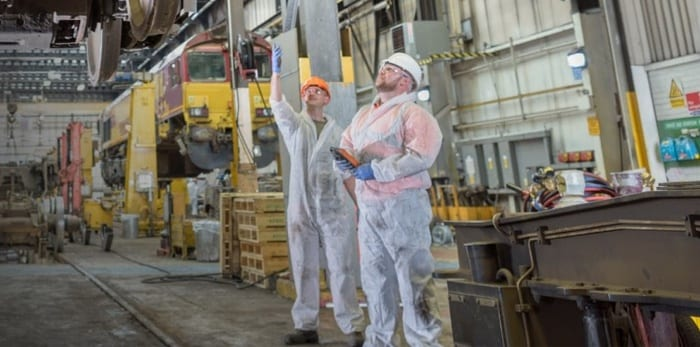 Two engineers working with safety clothes