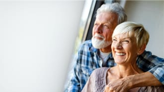 Three quarter view of older couple looking off camera and smiling.