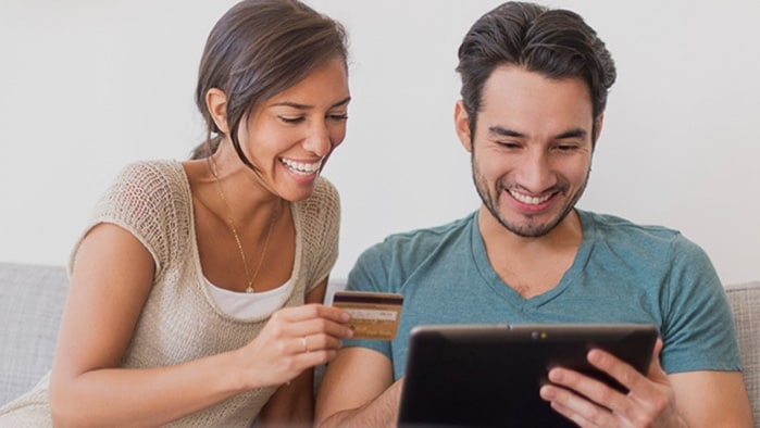 A smiling couple holding a credit card and a table