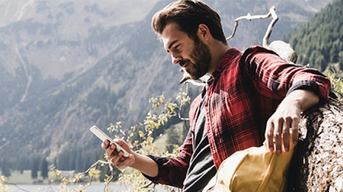 Man using smartphone outdoors in nature
