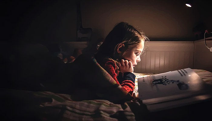 A child looking at books while in bed