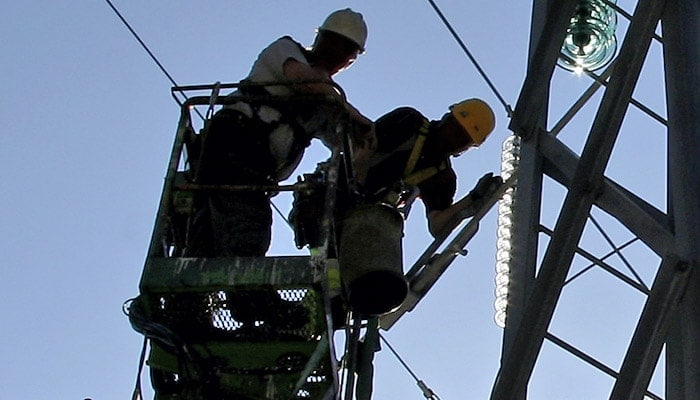 Two men in safety gear working on a power line