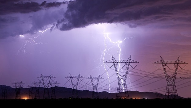 Series of power lines with lightning in the background