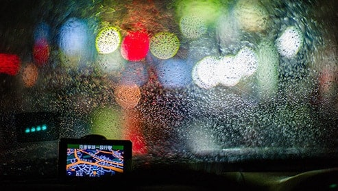 GPS in car with background of lights obscured by rain-covered windshield