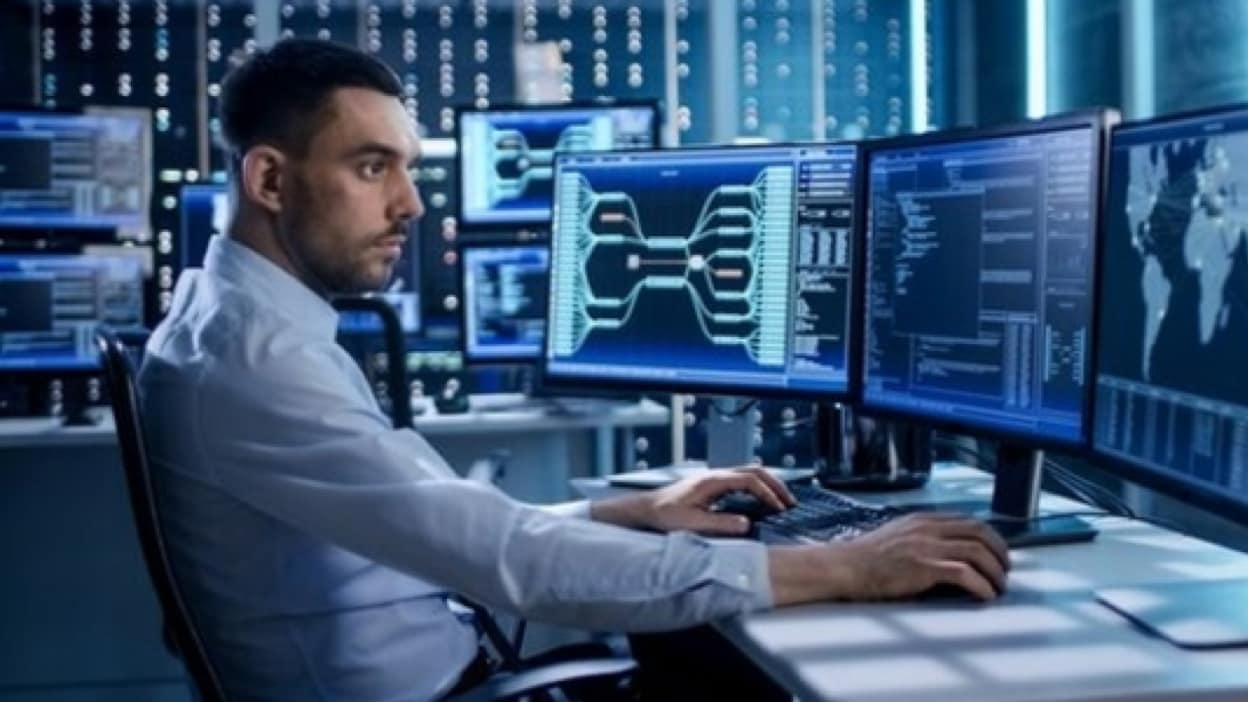 Business man at desk watching for cyber attacks on various systems across multiple screens in front of him