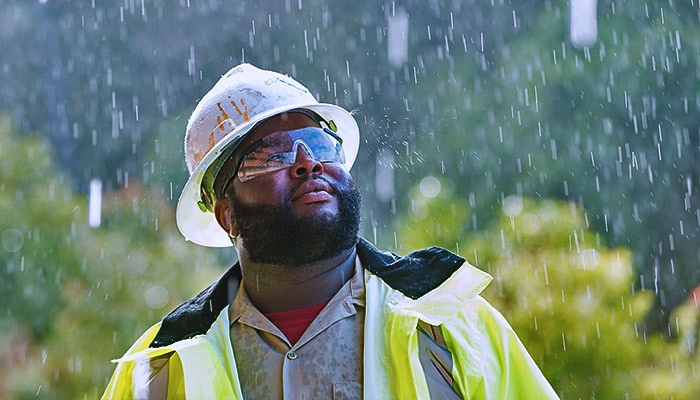 Worker in a hard hat looking up during a rain storm