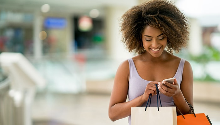 Woman holding packages looking at phone
