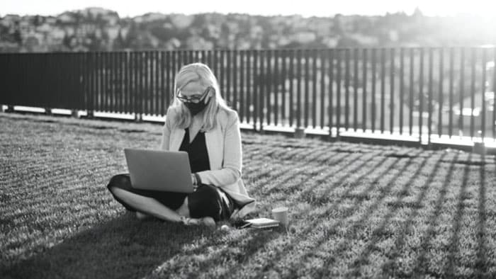 A woman wearing mask using a laptop while is sit on the grass and the sun is behind