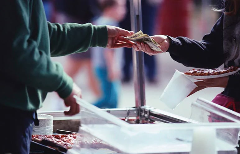 Person buying food and giving money to the salesperson