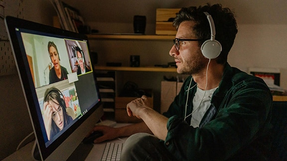 Man wearing headphones in a group chat on a desktop computer