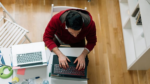 Overhead view of man working at laptop on table