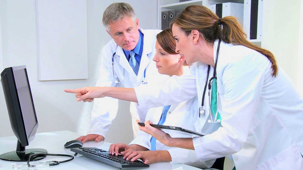 3 doctors looking to a screen computer, one of them is pointing to the sceen