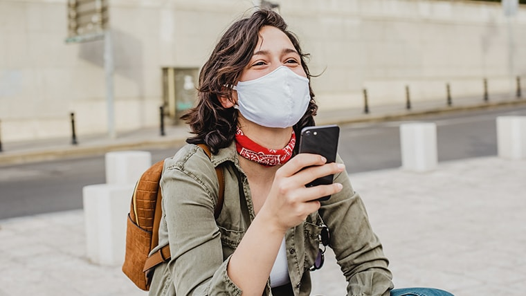 Person talking on a smartphone and wearing a mask