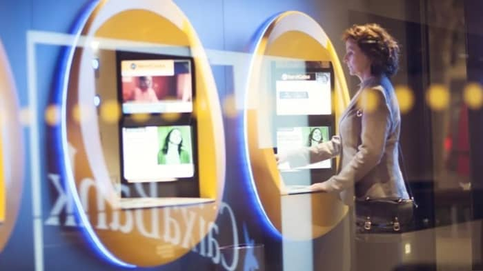 A woman using a kiosk in a bank