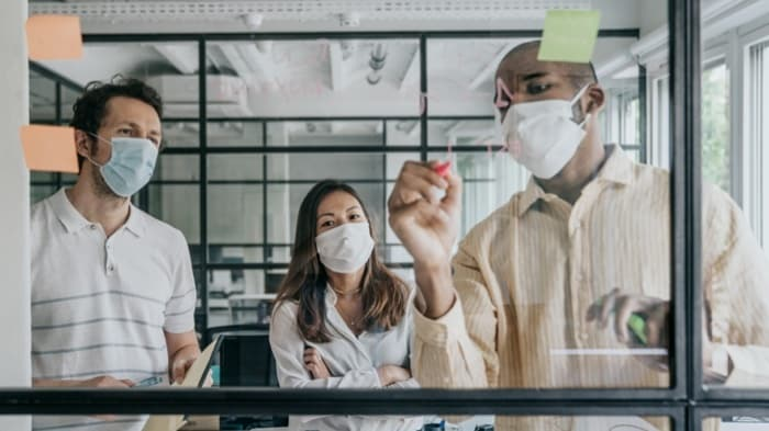 Three people wearing masks working on an agile board