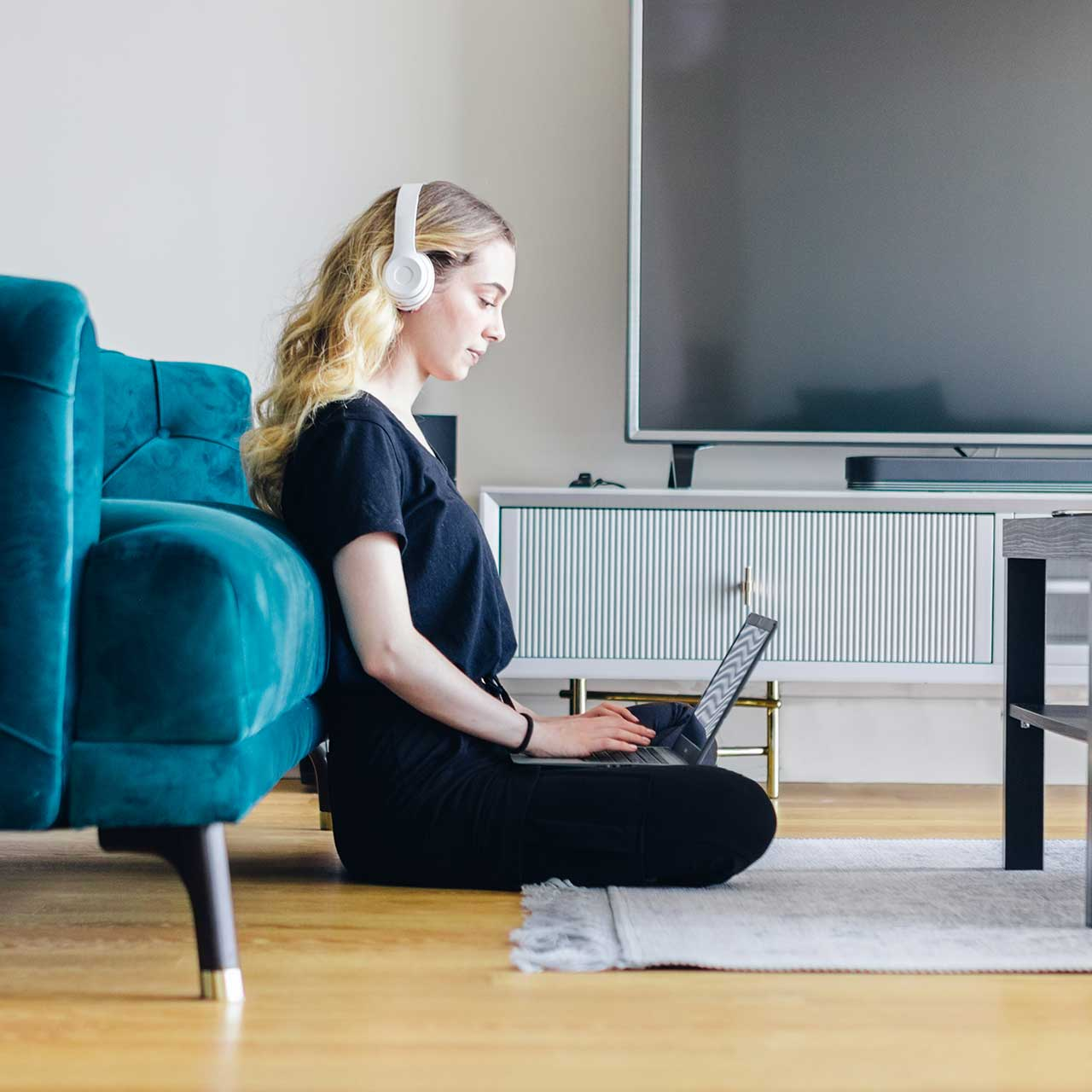 Person at home with headphones using laptop computer