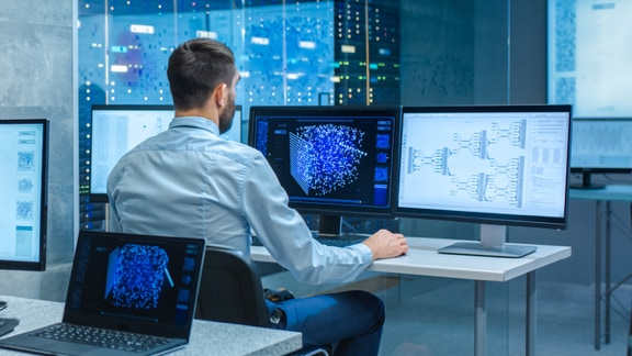 Man looking at screens in a cloud data center