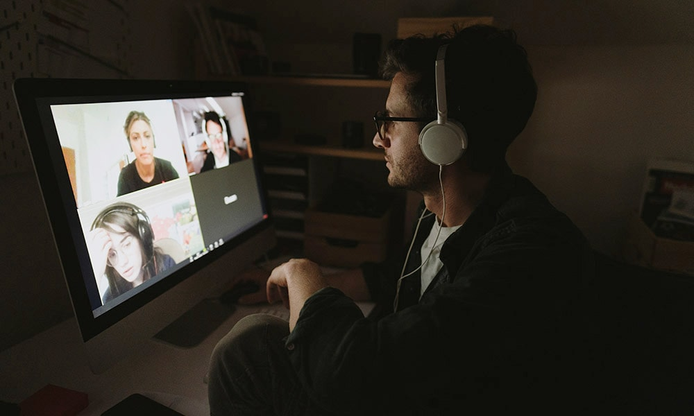 Man with headphones attending a online conference