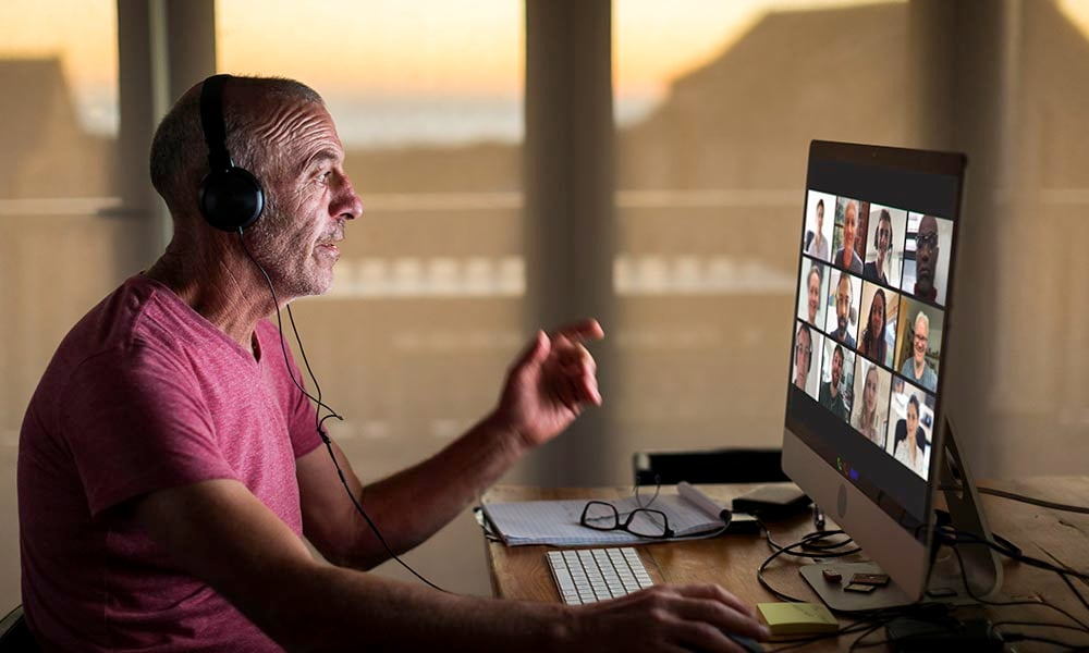 Older man with headphones attending a online conference