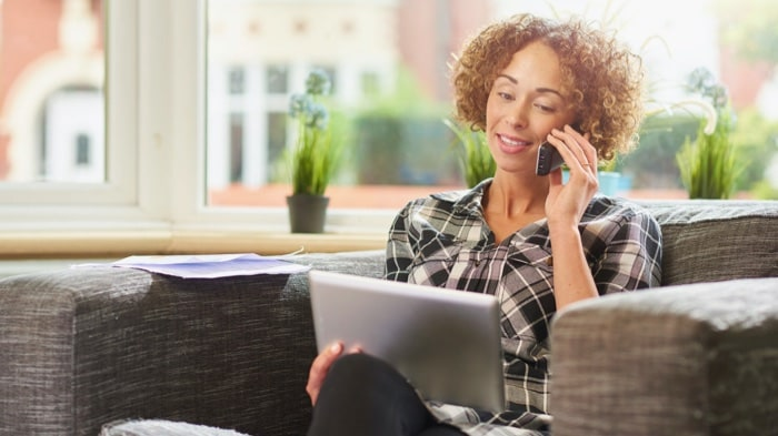 a woman on a couch making a call