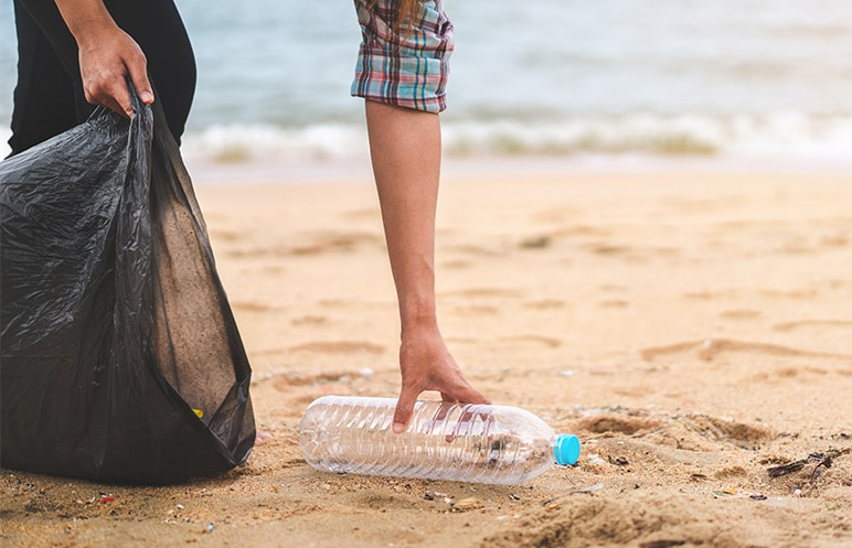 Man picking up a plastic bottle on a beach