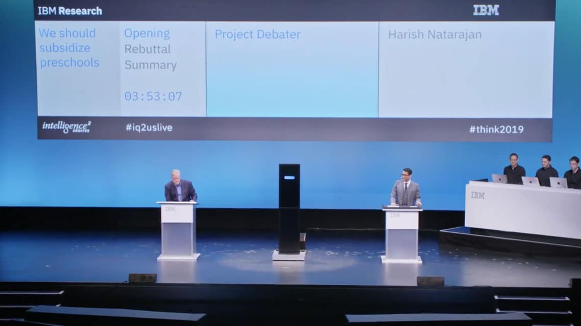 Debaters on stage with an AI construct