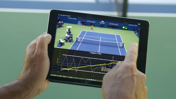 Hands manipulating video of tennis match captured on an electronic tablet