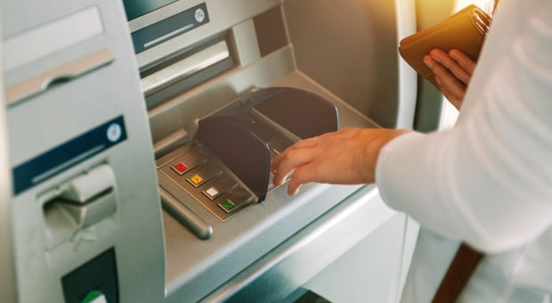 Close up of person using a bank ATM machine