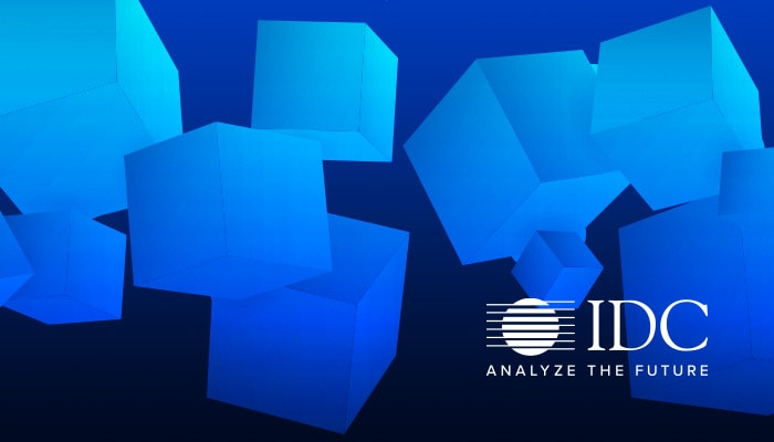 Abstract blue cube graphic with the IDC logo overlaying it