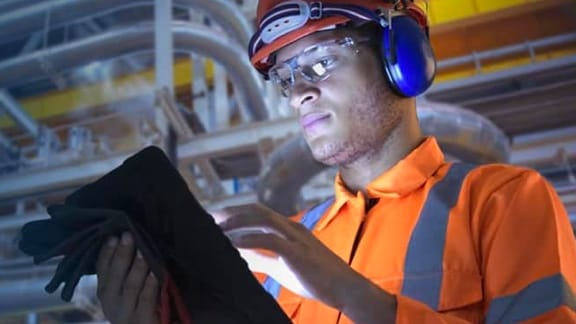 worker in hardhat with tablet