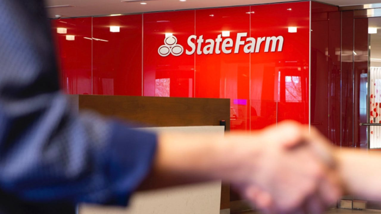 shaking hands in front of StateFarm store front
