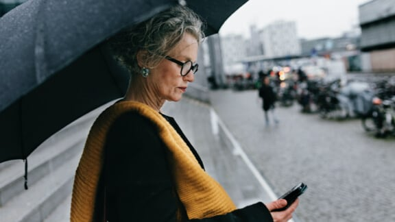 Woman under an umbrella looking at her phone