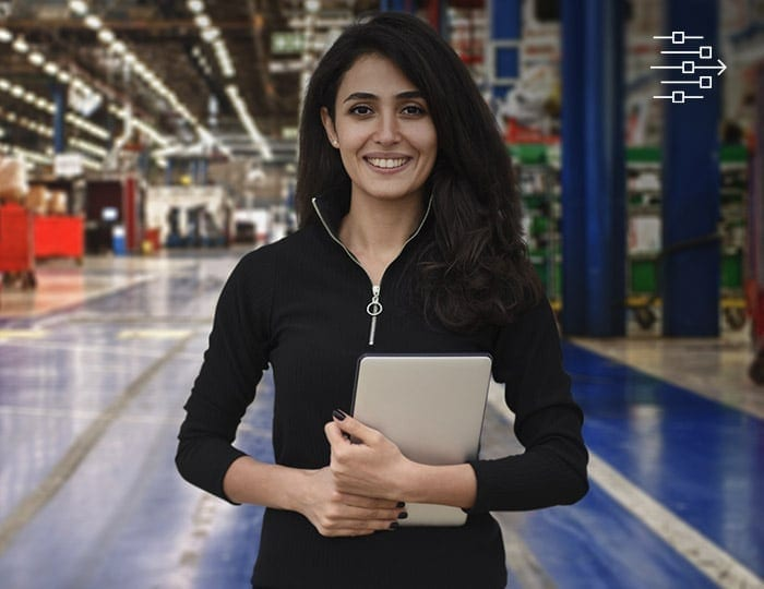 Young woman holding a tablet standing on a factory floor