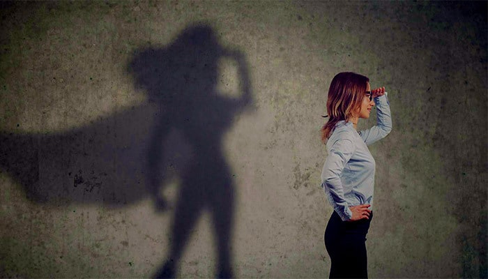 Woman looking in distance with superhero shadow