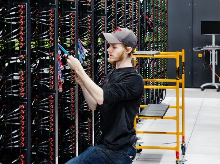 Young man with beard wearing a cap and connecting cables in a room with several IT hardware