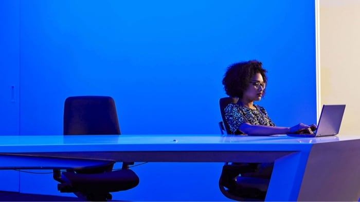 Woman on laptop in room conference table with blue hues