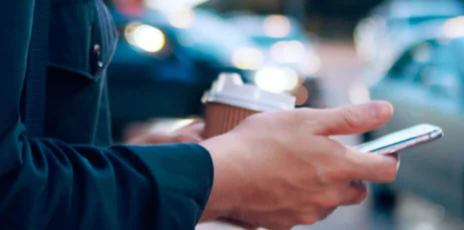 A person using a smartphone while taking a coffee