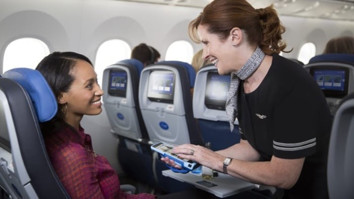 flight attendant and passenger smiling together