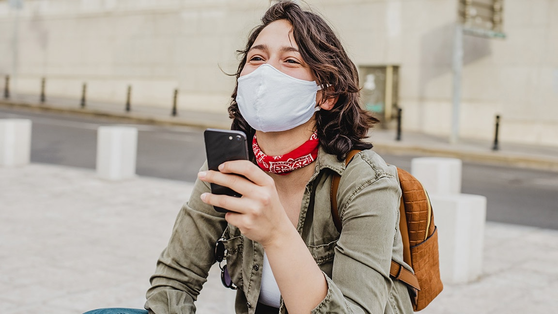 Happy person outside using a mask with a smartphone in hands